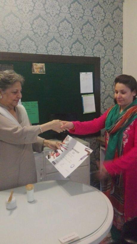 A participant, Ms. Farzana from Gupis receiving certificate of training from Apa Daulat Rahimtoola